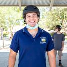 Student poses wearing a helmet and mask.